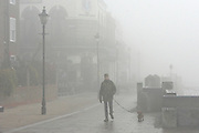 © Licensed to London News Pictures. 11/12/2013. London, UK. A man walks along a fog shrouded street.  Fog along the banks of the River Thames in Hammesmith, West London this morning 11th December 2013 . Photo credit : Stephen Simpson/LNP