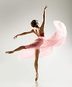 Classical female ballet dancer, Jackie Bologna, in a pink romantic tutu in the photo studio on a grey background. Photograph taken in New York City by photographer Rachel Neville.