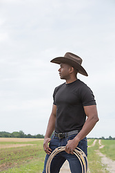 African American cowboy with a lasso on a ranch