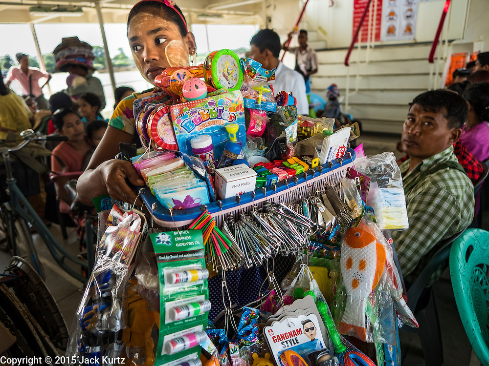 30 OCTOBER 2015 - YANGON, MYANMAR:  A woman selling toys, cigarettes and notions on the Dala ferry. The ferry to Dala runs continuously through the day between Yangon and Dala. Yangon, Myanmar (Rangoon, Burma). Yangon, with a population of over five million, continues to be the country's largest city and the most important commercial center.          PHOTO BY JACK KURTZ