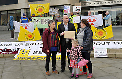 © Licensed to London News Pictures. 30/11/2011. Bristol, UK. Left-right: Anti-nuclear campaigner Katy Attwater, Mark Wilson IPC Principal Case Manager for Hinkley C, campaigner Nikki Clark with daughter (name withheld).   Anti-nuclear campaigners handed in their objections against the building of a new nuclear power station at Hinkley Point in Somerset. to the Infrastructure Planning Commission at Temple Quay House in Bristol..Photo credit : Simon Chapman/LNP