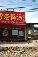 "China, Beijing, Chaoyang, San Jian Fang, 2008. View of a restaurant protesting forcible eviction by using ""death"" wreaths, traditionally reserved for funerals. Superstition may have prevented authorities from demolishing this building.."