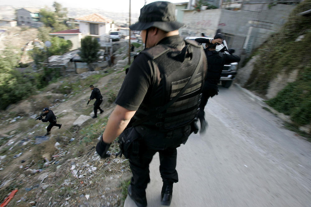 Tijuana Police agents in route to search a home for illegal contraband during a drug sweep in Colonia Chula Vista in Tijuana, Mexico.(Photo by Sandy Huffaker for the SF Chronicle)