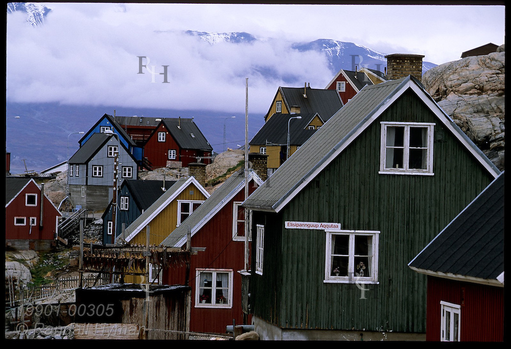 Colorful, Danish-style wooden homes line rocky slopes of Uummannaq, once a renowned whaling town; western Greenland