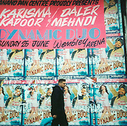 Man walking past a wall covered with posters advertising Karisma Kapoor and Daler Mehndi 'The dynamic duo' Sunday 25th June at Wembley Arena