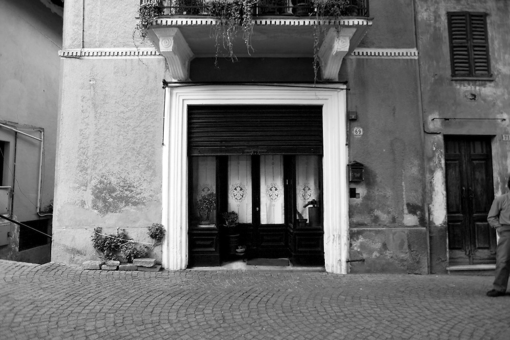 Entryway to a Barolo, Italian facade, Italy storefront in the Alps, with dual doorway with long window panes flanked by two more window panes on either side.  Identical oval design in center of windows. Brick paved street in front of home, Patio or porch hanging over doorway with plants flowing over the edge.