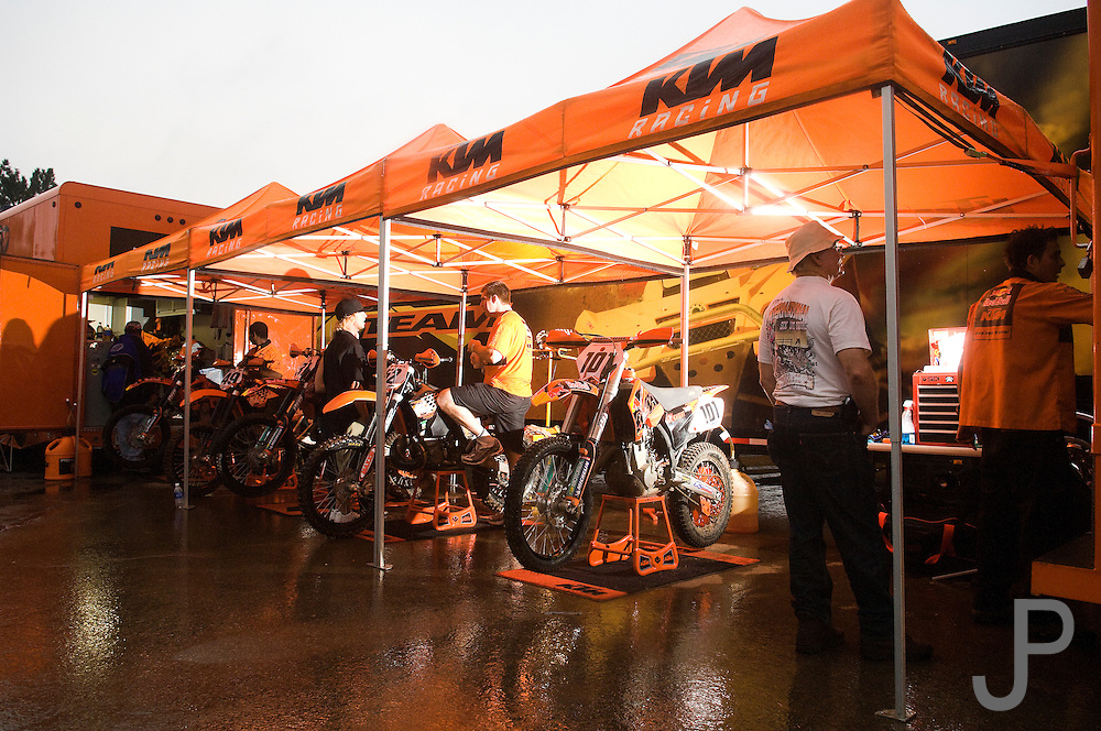 Eventual winner David Knight (tall rider in the middle) talks to mechanic in the KTM pits prior to the 2007 Maxxis AMA Endurocross at the Lazy E Arena in Guthrie, Oklahoma.  Event was won by David Knight #101 on KTM