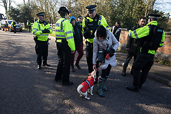 Denham, UK. 6 February, 2020. Police officers move on environmental activists from Save the Colne Valley, Stop HS2 and Extinction Rebellion who were walking at a snail's pace along a road so as to block for several hours a security vehicle and truck delivering fencing and other supplies to be used for works associated with the HS2 high-speed rail link close to the river Colne at Denham Ford. Some activists also collected litter during the action.