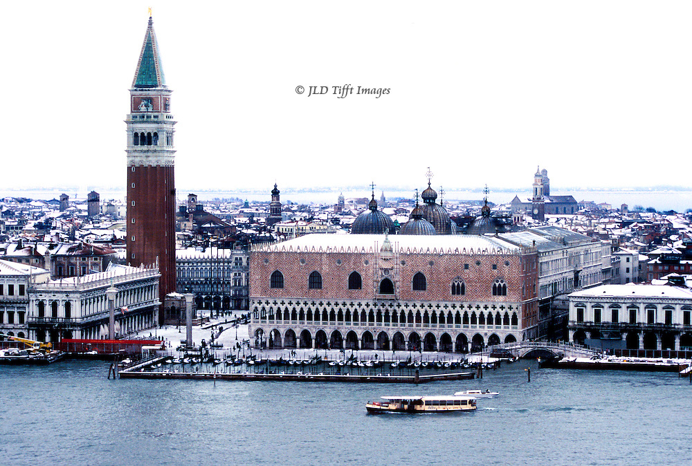 Venice under snow seen from the campanile of the Palladian church of San Giorgio Maggiore.  View across the laguna to the Doges' Palace, Campanile, and piazza di San Marco.  One vaporetto is passing along the water in front of the Doges' Palace..
