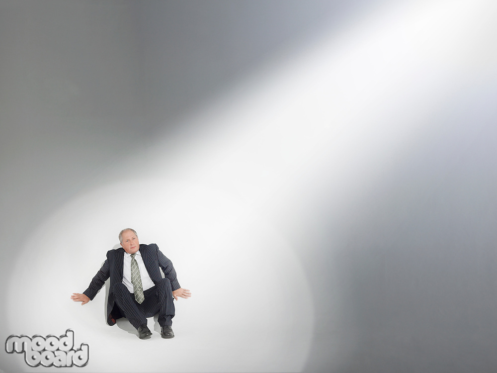 Businessman sitting looking up at source of spotlight