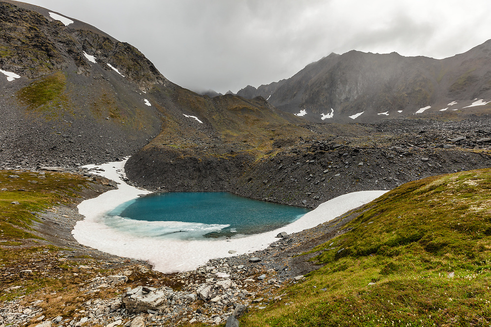 Winter's remnant snow at tarn in Palmer Creek Valley in Southcentral Alaska. Summer. Afternoon.