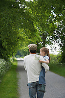 Father and daughter (5-6) embracing on country lane