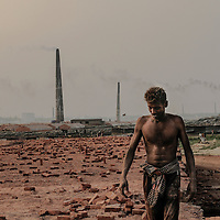 A man leaving  a brick field after  a day of work Ashulia, near Dhaka, Bangladesh.<br /> <br /> Ranging in age from pre-teens to grandparents, they work long hours to churn out millions of bricks to fuel a construction boom.