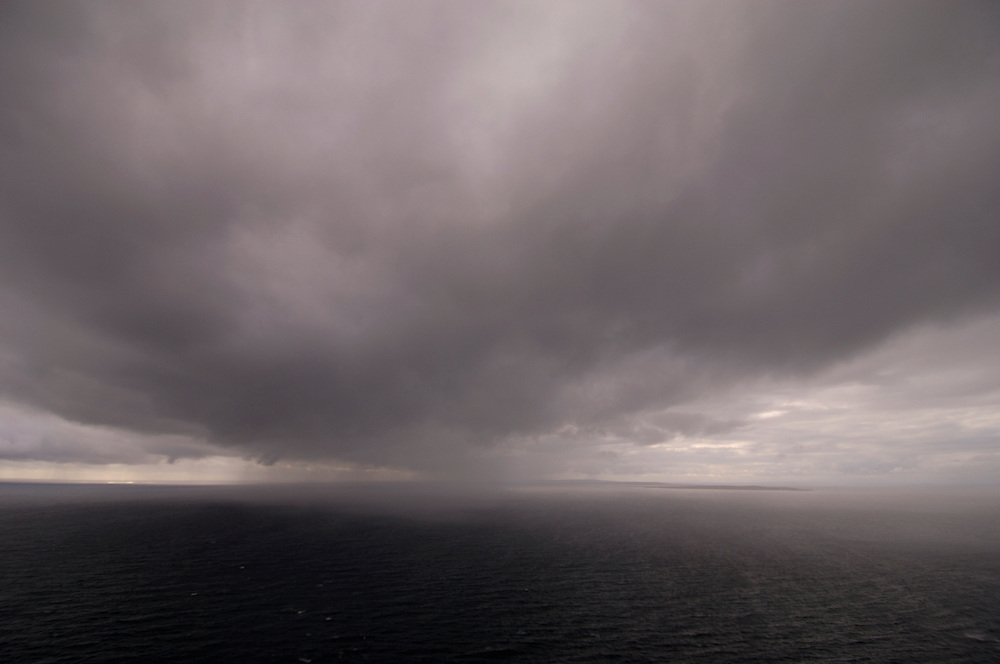 dark grey gray storm rain cloud sea squall approaching over sea. On horizon are the Aran Islands in Galway Bay west Ireland