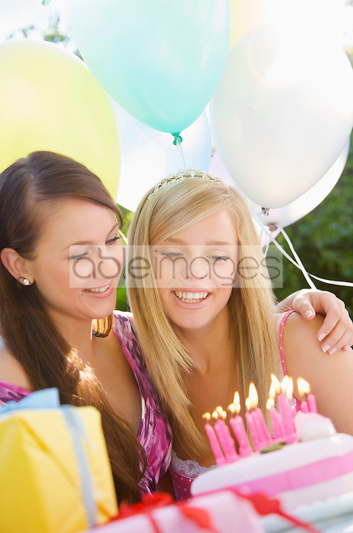 Close up of two smiling teenaged girls at birthday party