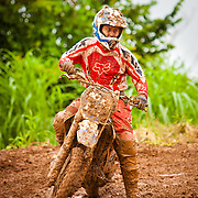 Front view of motorcycle and rider drenched in mud after passing through puddles of water on an outdoor motocross race track in Belmopan, Belize.