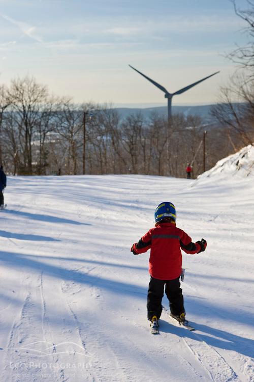 A young skier near the wind turbine at Jiminy Peak ski resort in the Berkshire Mountains in Hancock, Massachusetts.