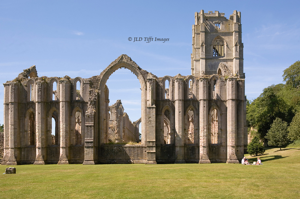 Yorkshire, Fountains Abbey ruins: exterior of east front; family picknicking at one corner.