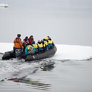 A zodiac with tourists breaks through a thin sheet of sea ice near Galindez Island in Antarctica.
