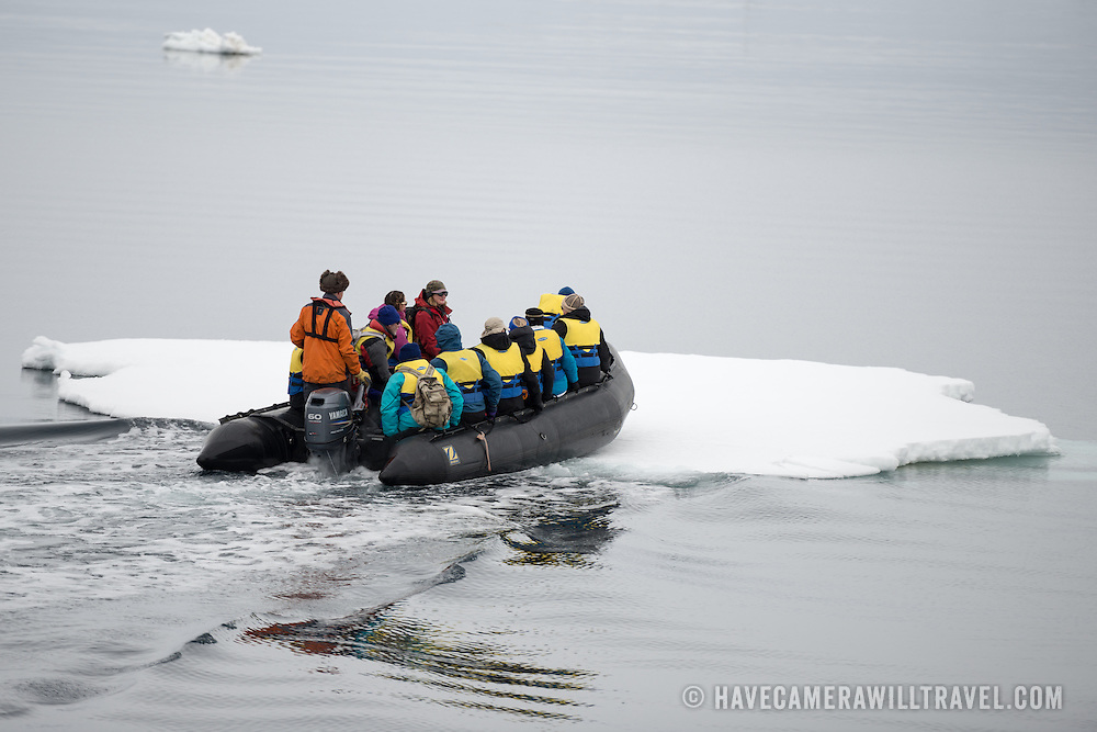 A zodiac with tourists breaks through a thin sheet of sea ice near Galindez Island in Antarctica.