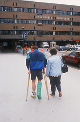 Patient using crutches walking to hospital,