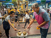 03 SEPTEMBER 2015 - BANGKOK, THAILAND: People light candles and incense at the Four Faced Brahma statue at Erawan Shine. Repairs to Erawan Shrine were completed Thursday, Sept 3 after the shrine was bombed on August 17. Twenty people were killed in the bombing and more than 100 injured. The statue of the Four Faced Brahma in the shrine was damaged by shrapnel and a building at the shrine was damaged by debris.      PHOTO BY JACK KURTZ