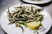"NAPLES, ITALY - 12 SEPTEMBER 2018: Fried anchovies are seen here at the Taverna del Buongustaio, a tavern in Naples, Italy, on September 12th 2018.<br /> <br /> Taverna del Buongustaio was founded in the 1930s by wine producer of the province of Caserta. Gaetano Aiese and his daughter Giusy have been managing the tavern since 1996. Customers of the Taverna are professors of the nearby University, students, merchants and employees of via Toledo, the commercial street right around the corner. Giusy and her father Gaetano decided to invest in the traditional Neapolitan cuisine. ""I learned cooking from my dad. And my dad learned cooking from his mother"", Giusy said."