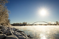 The Skipping Stone Bridge from Calgary's East Village to St. Patricks Island on a cold sunny day in winter. The Ice Fog drifting across the river glowing in the sun.<br /> <br /> &copy;2014, Sean Phillips<br /> http://www.RiverwoodPhotography.com