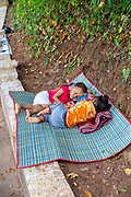 Two young girls nap on a mat while their mothers sell gifts to tourists at the famous Pak Ou Caves, Laos.