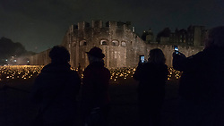 "© Licensed to London News Pictures. 05/11/2018. LONDON, UK.  Members of the public view a new installation by designer Tom Piper called ""Beyond the Deepening Shadow: The Tower Remembers"", open at the Tower of London until Armistice Day 2018.  The moat is filled with thousands of individual flames commemorating the centenary of the end of the First World War.  Yeoman Warders, former servicemen and women, ceremonially lit the first flame followed by volunteers proceeding to light the rest of the installation, gradually creating a circle of light, radiating from the Tower.  Photo credit: Stephen Chung/LNP"