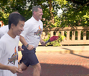 On Lam(left), owner of Lam's Garden, Ahens, Rick Crossen(middle), Athens City Police, Steve Noftz(right with torch), Ohio University Police..They run up Richland avenue, as the start of Day 1 of the Law enforcement Torch Run on 6/24/04 which will end at OSP Post 23 on Ety Rd in Lancaster, OH. This event is to raise awareness and money for special olympics