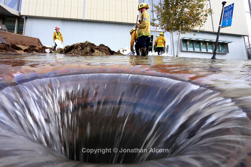 Firefighters work near an open drain on the UCLA campus, which was flooded by a broken thirty inch water main in the Westwood section of Los Angeles July 29, 2014. The  100-year old water main flooded parts of the campus and stranded motorists on surrounding streets.  Jonathan Alcorn