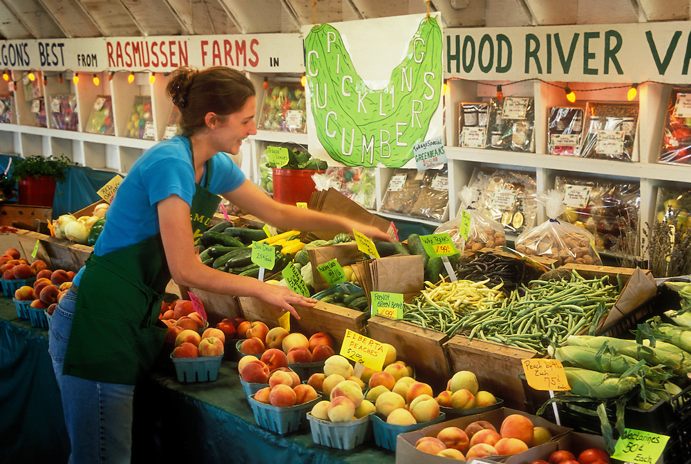 Rasmussen Farms fresh produce stand in the Hood River Valley, Oregon; summer worker Jennifer Elkington stocking shelves.