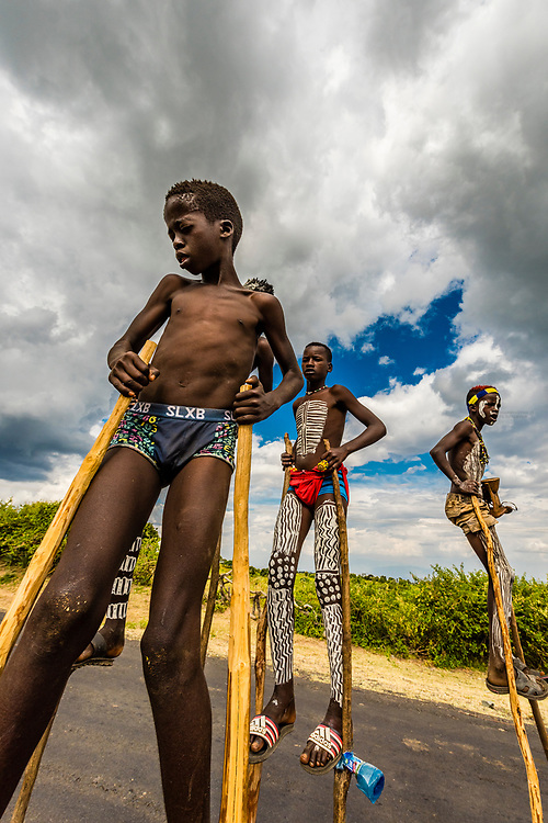 Bena tribe boys walking on stilts near Key Afer, Omo Valley, Ethiopia.