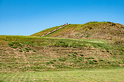 Monks Mound is the largest prehistoric earthwork in the Americas. Cahokia Mounds State Historic Site preserves the largest prehistoric Native American city north of Mexico. Cahokia existed circa 1050–1350 CE, in what is now southern Illinois between East St. Louis and Collinsville, across the Mississippi River from modern St. Louis, Missouri, USA. The present park contains about 80 manmade earthen mounds, but at its apex around 1100 CE, Cahokia included about about 120 mounds and covered 6 square miles (16 km2) with a population briefly greater than contemporaneous London. Cahokia was the largest and most influential urban settlement of the Mississippian culture, which developed advanced societies across much of what is now the central and southeastern United States, beginning 1,000+ years before European contact. Cahokia Mounds is one of 24 UNESCO World Heritage Sites within the United States, and is the largest archaeological site north of the great pre-Columbian cities in Mexico.