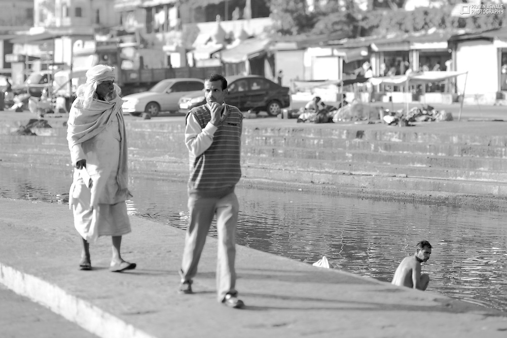 PEOPLE & SADHUS AT RAMKUNDA, IN MORNING, PANCHAVATI, NASHIK INDIA. Shot using tilt shift lense to creat illusion of focus.