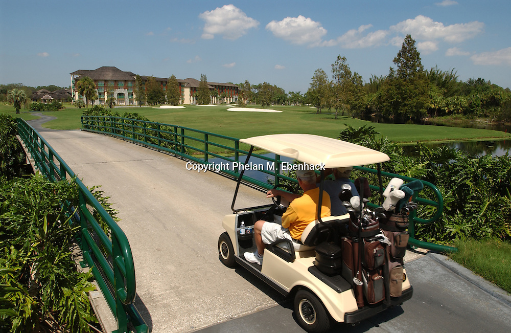 Two golfers drive over the bridge down the fairway to the 18th. green on the Palm golf course at the Walt Disney World Resort in Lake Buena Vista, Florida.
