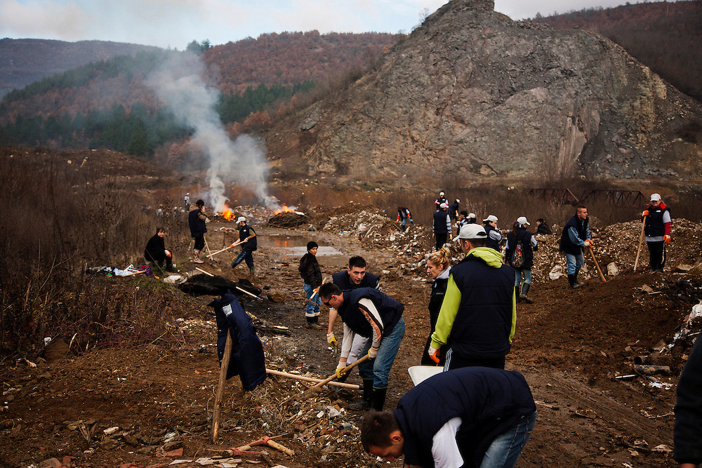 Youth from Kosovoska Mitrovica work to clear a back road of debris and trash on a USAID funded project.