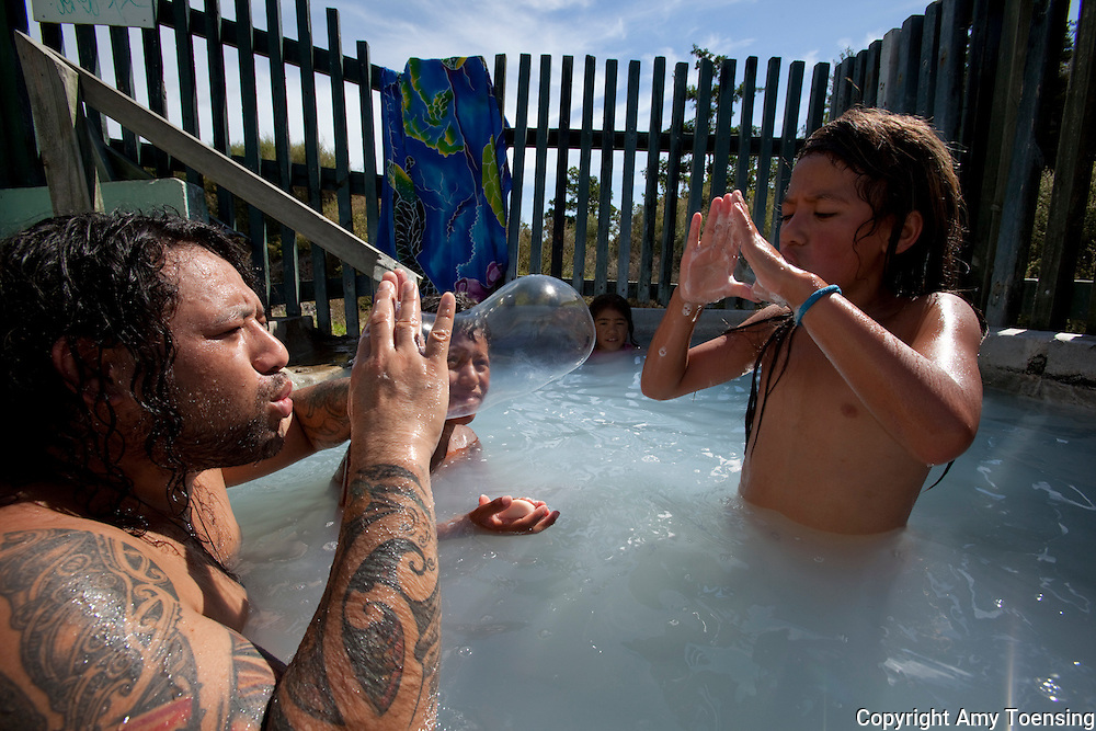 ROTORUA, NEW ZEALAND -- FEBRUARY 10: Jason Philips baths with his children in a the communal bath in the Whakarewarewa Village. Communal bathing is common in the Maori Villages in this thermal area where natural hot springs are everywhere. &quot;It's a time when you can catch up with all the news and gossip from your neighbors. It's also a relaxed and intimate time to spend with your kids - you can find out what's going on in their lives.&quot;..KIDS:.Angelina.Fraser (youngest).Tehurinui (heavier, older)..CONTACT:.Jason Philips 021 0237 72224...Photo By Amy Toensing _________________________________<br />