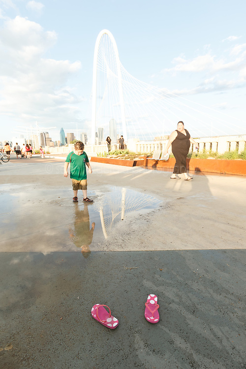 Kids playing near puddle and pink flip flops. On Continental Avenue Bridge with Margaret Hunt Hill Bridge in background, Trinity River, Dallas, Texas, USA.