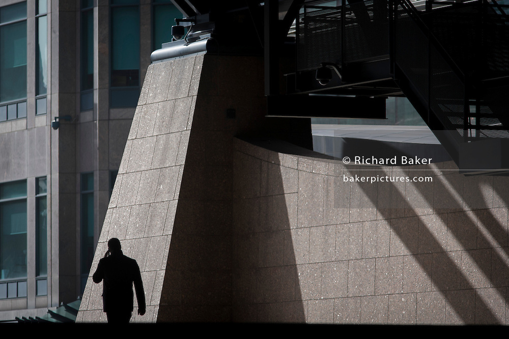 Single silhouette of man walking through the Broadgate corporate offices development in the City of London.