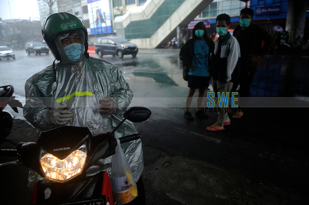 Medan, Indonesia, March 28, 2020: A worker of online delivery service activities seen under the rain at the main road of Medan beside the daily socialization and disinfection of the Corona Virus Disease 19 spread dangers in North Sumatra province, Indonesia on March 28, 2020.