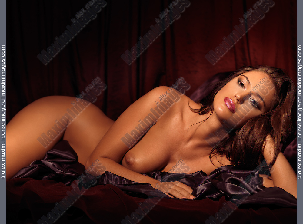 Classic artistic nude photo of a Beautiful sensual young woman lying naked in bed