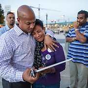 10/03/2013  ROXBURY, MA    Isaura Mendes (cq) (center) was comforted by former mayoral candidate John Barros (cq) (left) outside the Boston Police District B-2 Headquarters in Roxbury following yesterday's death of her nephew Leroy Carvahlo (cq).  (Aram Boghosian for The Boston Globe)