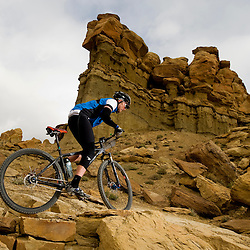A racer climbs a rocky section with a great view.