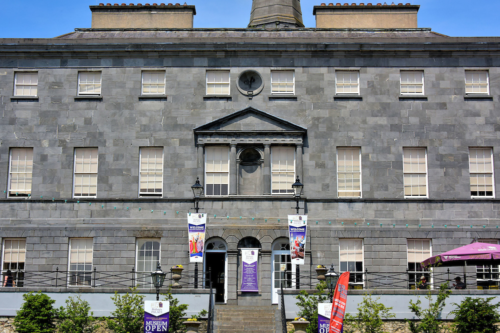 Bishop's Palace Museum in Waterford, Ireland<br /> The Bishop of Waterford commissioned architect Richard Castles to build this impressive Georgian structure. You cannot miss this 1741 landmark along The Mall. Below the terrace in the foreground is part of the city's original city wall. The historic building opened as the Bishop's Palace Museum in 2011. Inside you will learn the story of Waterford from 1700 through the 1970s. Included are displays of period furniture, artifacts and artwork. They are arranged as if you were walking through an elaborate 18th century townhouse. The museum is part of a trilogy called Waterford Museum of Treasures.