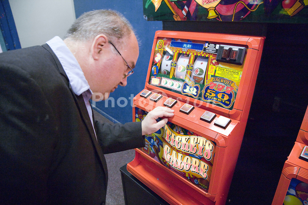 Man looking at slot machine in amusement arcade whilst on a day whilst on a day trip to Skegness organised by Nottingham Disabled Friendship Club,