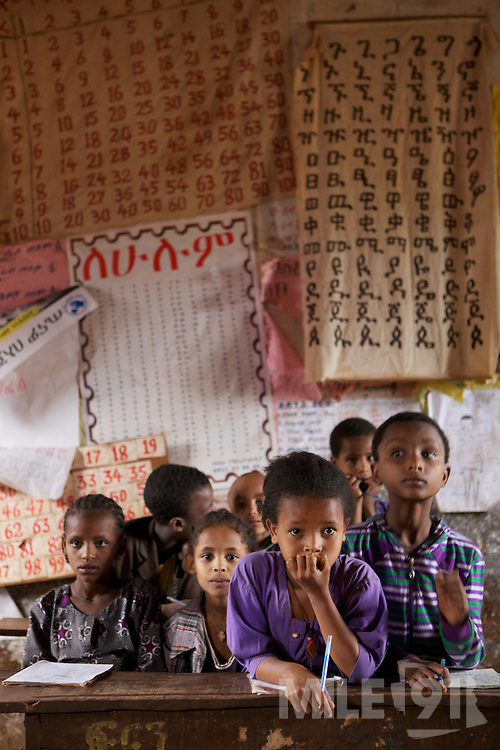School children learning inside a model classroom in Finote Selam, Ethiopia. Notice all the teacher learning materials on the wall. This is a good example of some of the results achieved by VSO volunteers like Pat Gilhooley and James Elford, who are working at the local teacher training college training teacher trainers how to use more interactive learning methods and display the childrens work on the walls.