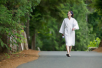 A spa client in her robe walks to her treatment while visiting the Kingfisher Resort and Spa.  Courtenay, Vancouver Island, British Columbia, Canada.