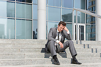Full length of stressed businessman sitting on steps outside office
